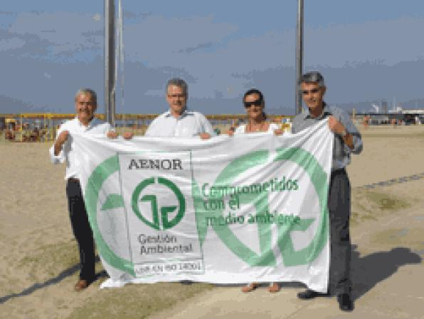 The flag of the ISO 14001 waves on the beach of Levante